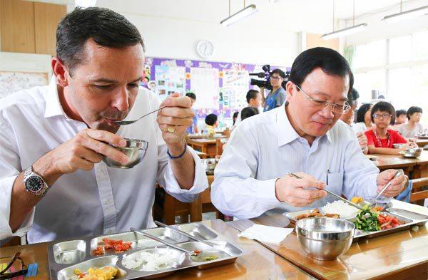 尼爾洛孚(左)到蘆洲成功國小與新北市農業局長廖榮清(右)及小朋友共享有機營養午餐...