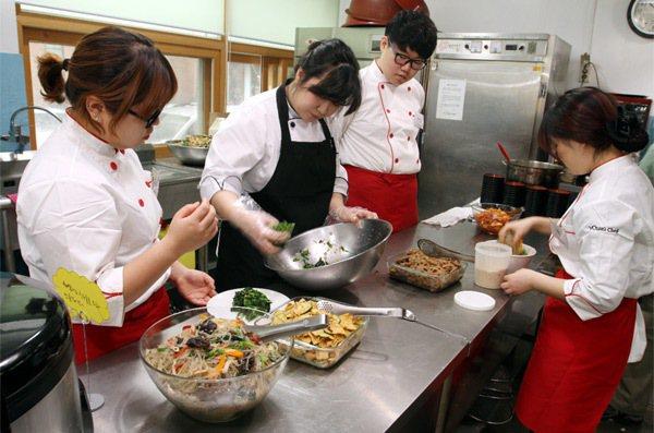 haja center學生在老師(左二)指導下準備午餐。 特派記者侯永全/攝影