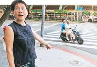 難忘喪子之痛的伯軒媽媽帶領記者在她家附近檢視行人的步行環境,指著被撞斷的車阻痕跡...