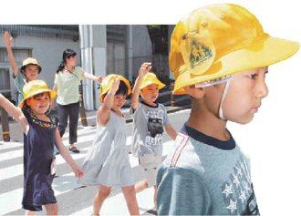 日本警察會到學校教小學生如何安全過馬路,舉手向駕駛人示意效果佳;小學生帽子上都別...