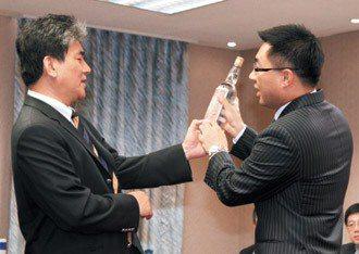 聯合報願景專題「公路正義 」在政壇引起回響。立委江啟臣(右)昨天拿出高粱酒,與內...