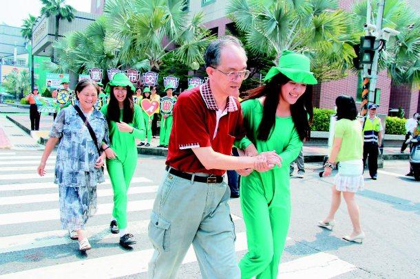 嘉義市交通安全月昨起跑,由學生扮成小綠人,扶長輩過馬路。 記者曹馥年╱攝影
