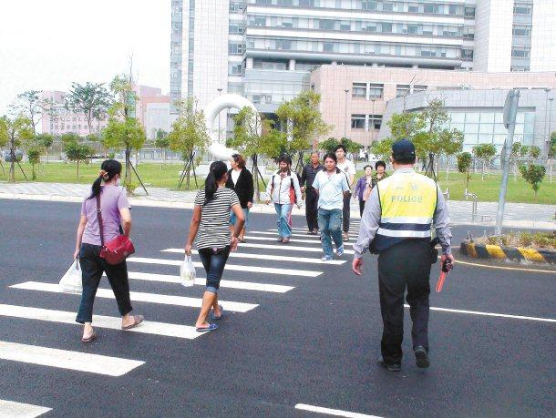 昨天交通大執法首日,嘉義縣警方加強宣導,請行人依號誌過馬路,民眾都很配合。 記者...