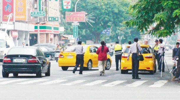 行人路權大執法首日,高雄市警方在中華路與大同路口攔下兩輛違規的計程車。 記者曹敏...