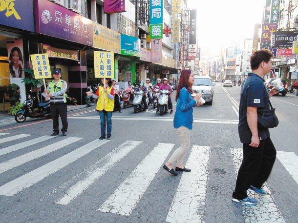 警察昨在重要路口執法,志工舉牌提醒駕駛禮讓行人,行人走斑馬線嘴角展露微笑。 記者...