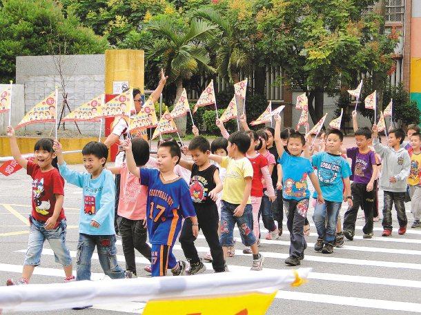 花蓮市明廉國小學童揮舞「禮讓小旗」安全過馬路。 記者范振和╱攝影