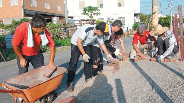 村民梁國棟(左一)帶領福興西勢村民鋪設人行道,大家用接力方式,一個接過一個磚頭,...