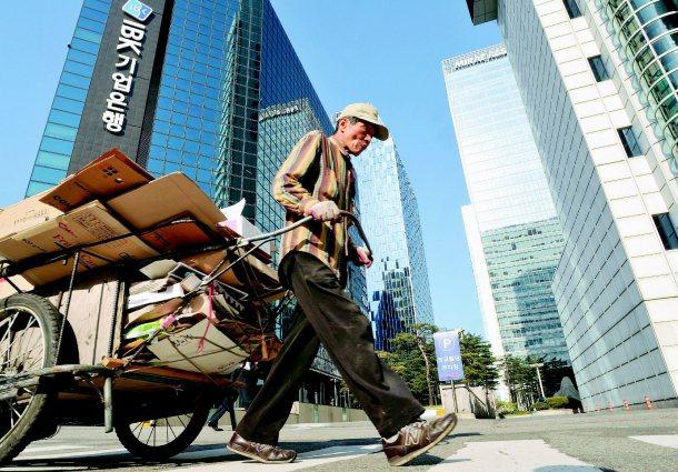 美韓FTA實施後,貧富差距擴大更受關注。一名老先生拖著整車的回收物品,穿越商業大...