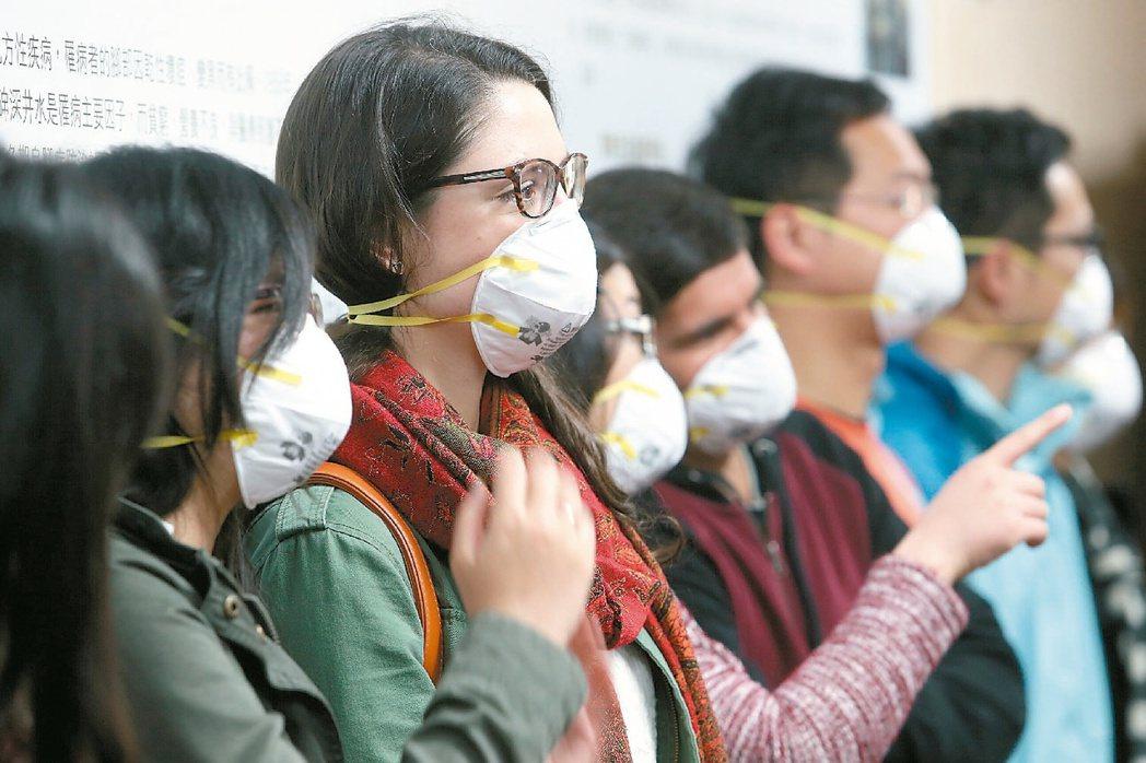 台大公衛學院「從PM2.5看我們的穹頂」記者會中,ㄧ同出席的學生載上N95口罩,...