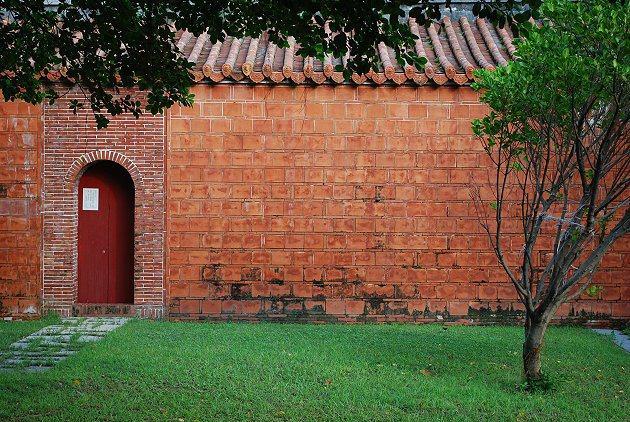 文武廟的庭院紅磚牆與百年古榕。 記者趙惠群/攝影