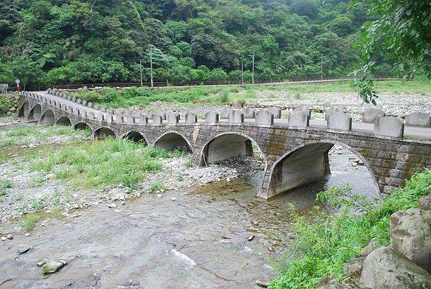 白鮑溪攔砂壩後方河床上有跨接兩岸的石拱橋,騎乘自行車十分愜意。 記者趙惠群/攝影