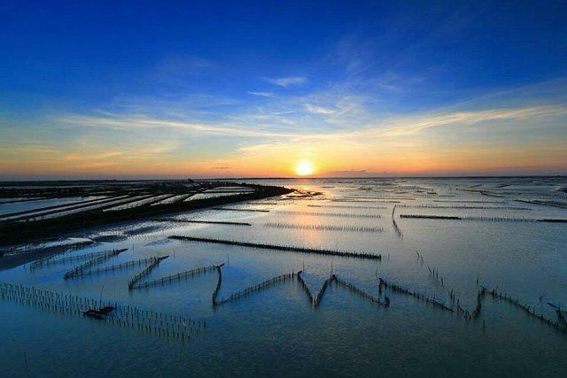 七股北堤堤岸平直開闊,海面與天空一覽無遺,水上還有魚塭和蚵架,黃昏向晚,拍起來構圖很美。 李御林攝影