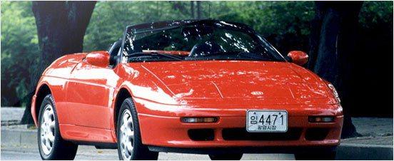 1996年,KIA買下蓮花小型敞篷車Elan的生產專利權,但投資並未成功,使得KIA營運財務更形吃緊。 KIA提供