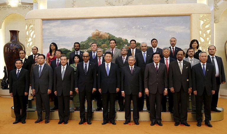 中國國家主席習近平去年十月在北京人民大會堂舉行的亞投行發起會議中,與參與的各國代...
