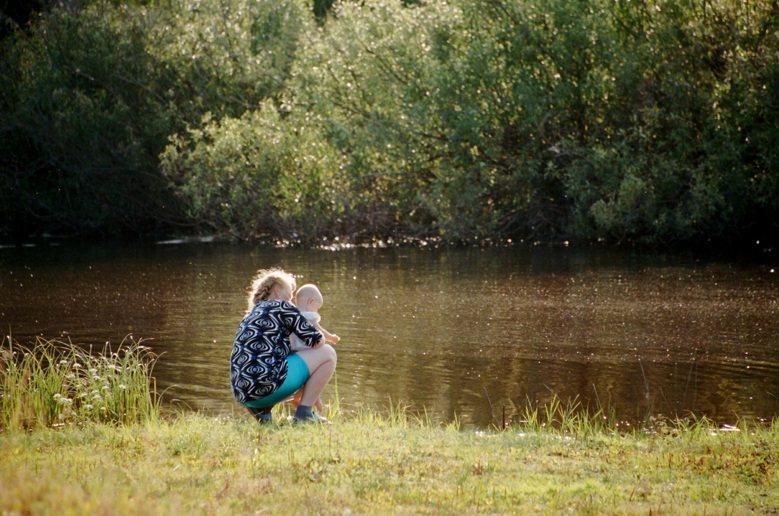 29年後的普里匹特河畔,母親試著讓初生嬰孩親近河水。 圖/林龍吟