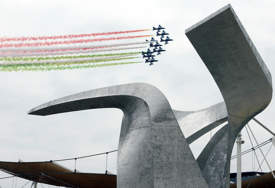 世博開幕儀式中,義大利空軍「三色箭特技小組」飛越會場上空,噴出代表義大利國旗的紅...