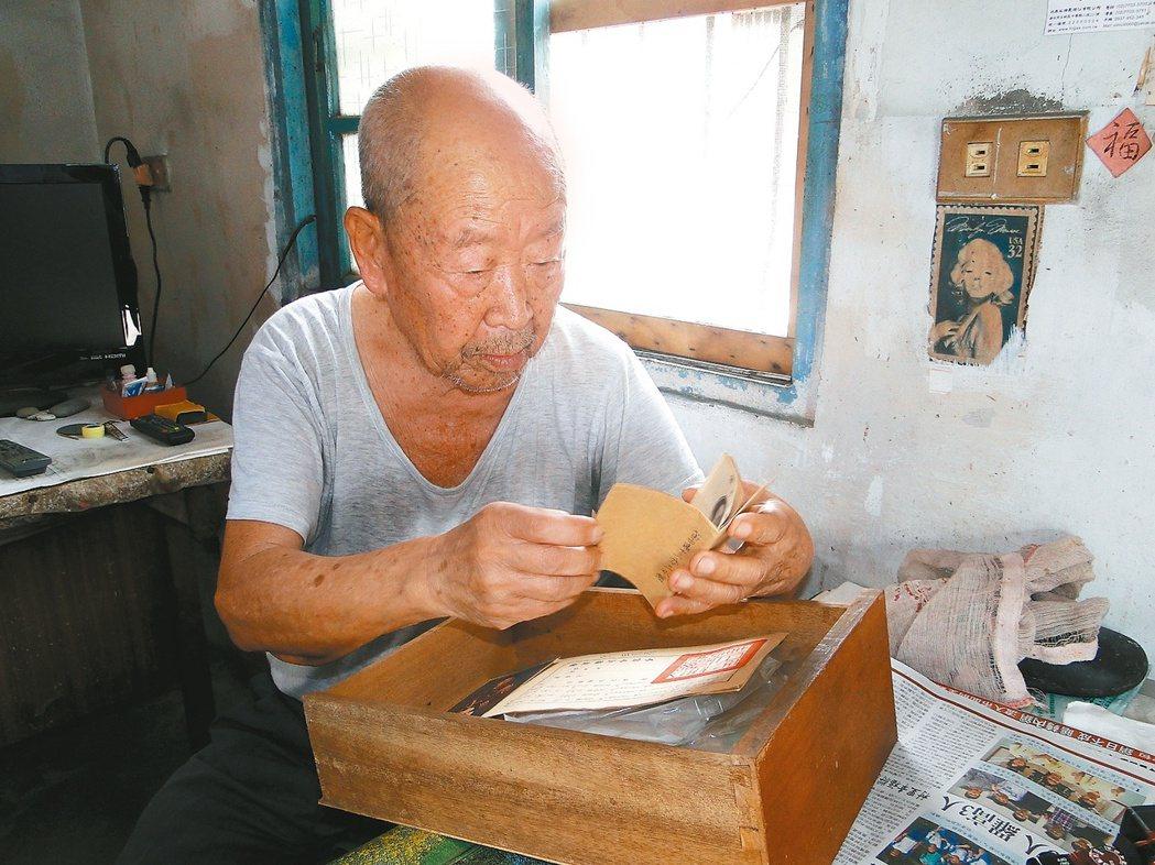 百歲抗戰老兵王從志看著他珍藏的當兵資料,他獨居的住處簡陋斑駁。 記者范振和/攝影