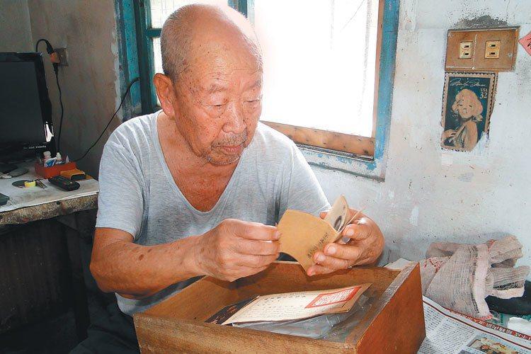 百歲抗戰老兵王從志看著他珍藏的當兵資料,他獨居的住處簡陋斑駁。 記者范振和/...
