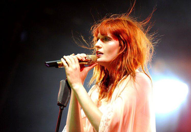 舞台上的Florence Welch是熱力四射的樂團主唱,紅髮在燈光照耀下變成亮...