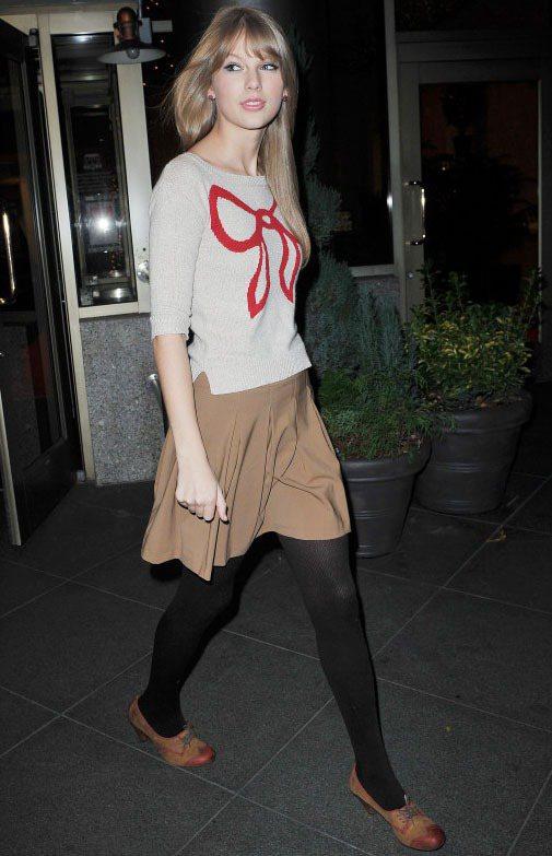 米色針織上衣印有紅色蝴蝶結,搭配駝色短裙與褲襪,很適合早春乍暖還寒的天氣。圖/達...