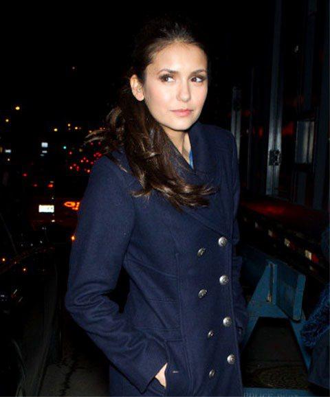 Nina Dobrev以洋裝搭大衣的氣質造型亮相,咖啡色眼妝點綴魅眼,不對鏡頭放...