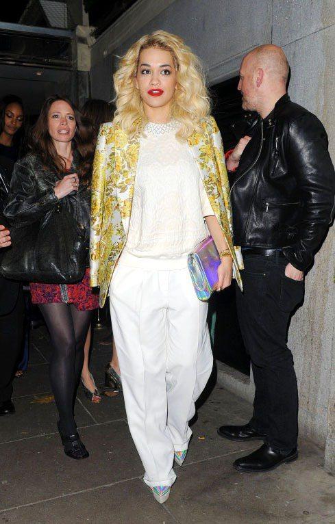 Rita Ora一身白色褲裝套裝,披上同色系刺繡裝飾外套,搭配散發炫彩光澤的手拿...