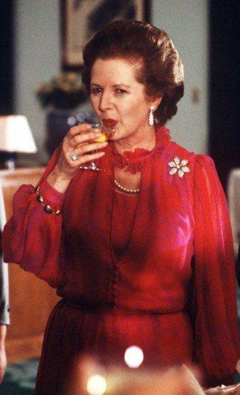 1982年造訪中國大陸的宴會上,一席紅色透膚長袖禮服搭配珍珠項鍊和各式小巧珠寶,...