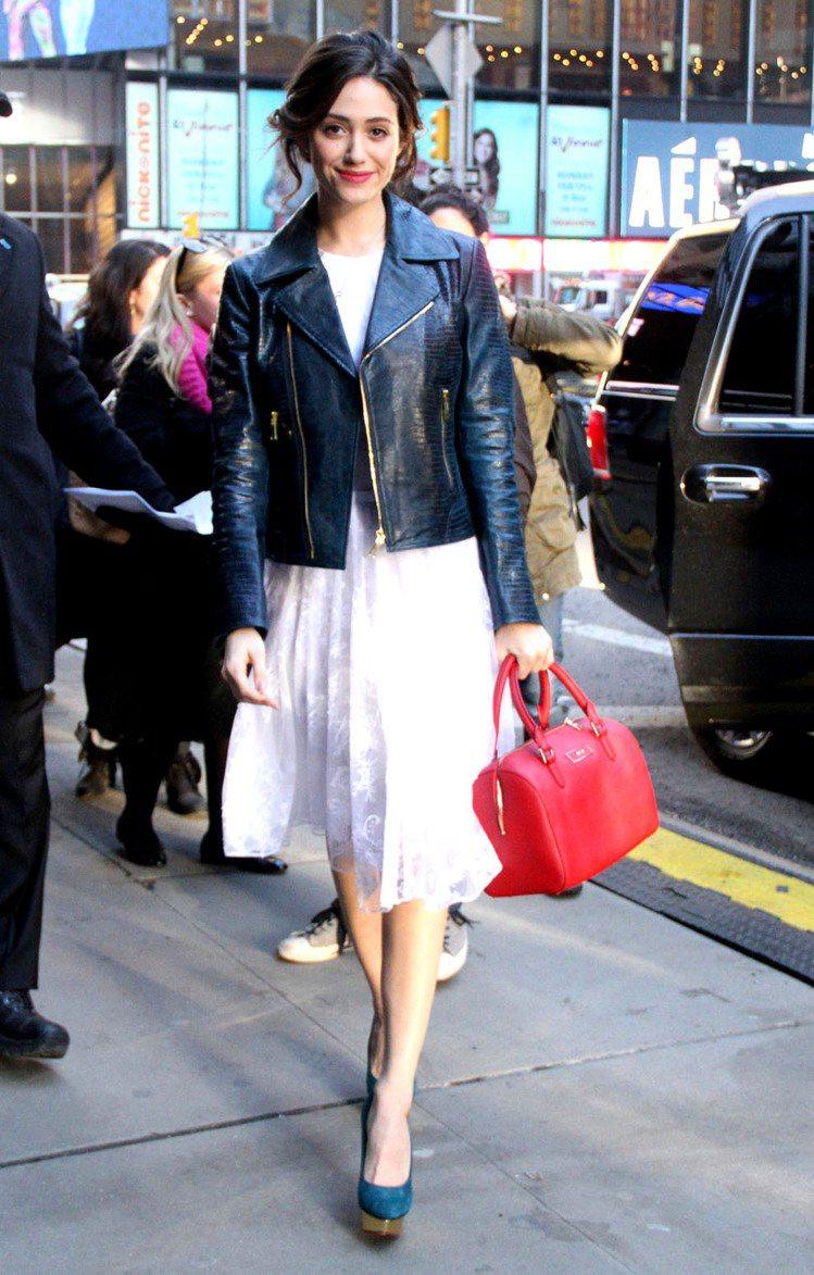 白色紗質蕾絲洋裝是許多女人的夢幻逸品,艾美羅森外搭一件深綠色皮夾克,手拎紅色波士...