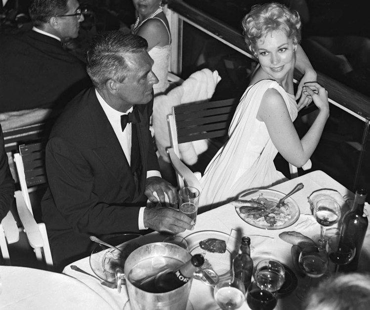 金露華(右)與卡萊葛倫在1959年一同出席坎城影展期間被記者拍下這充滿歷史性的瞬...