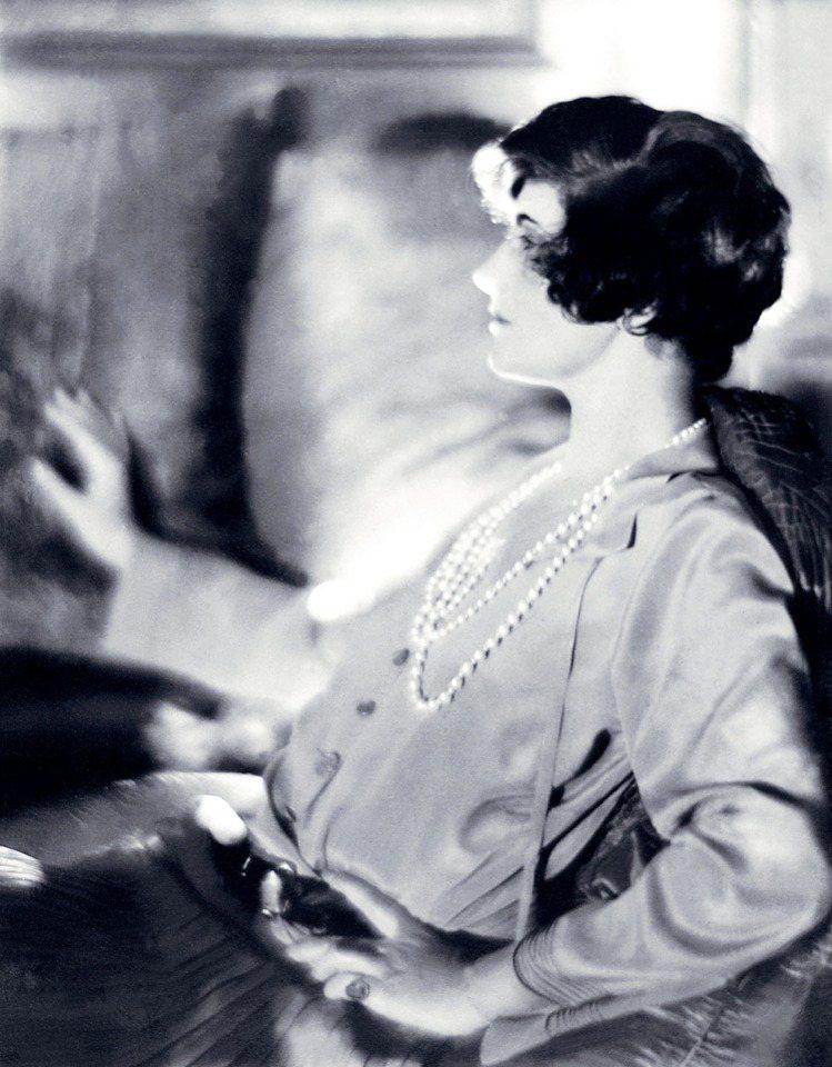 短髮的香奈兒,穿戴白色珍珠和一件緞質上衣,約1920年。圖/馬可孛羅文化提供