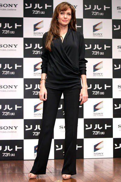 為《特務間諜》到東京宣傳的裘莉則是穿上黑色寬鬆垂墜上衣搭西裝褲,配她最愛的裸色高...