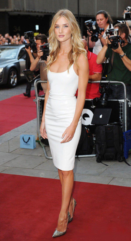 超模蘿西杭亭頓以簡單合身的Versace白色低胸連身裙亮相,一頭漂亮捲髮落在肩上...