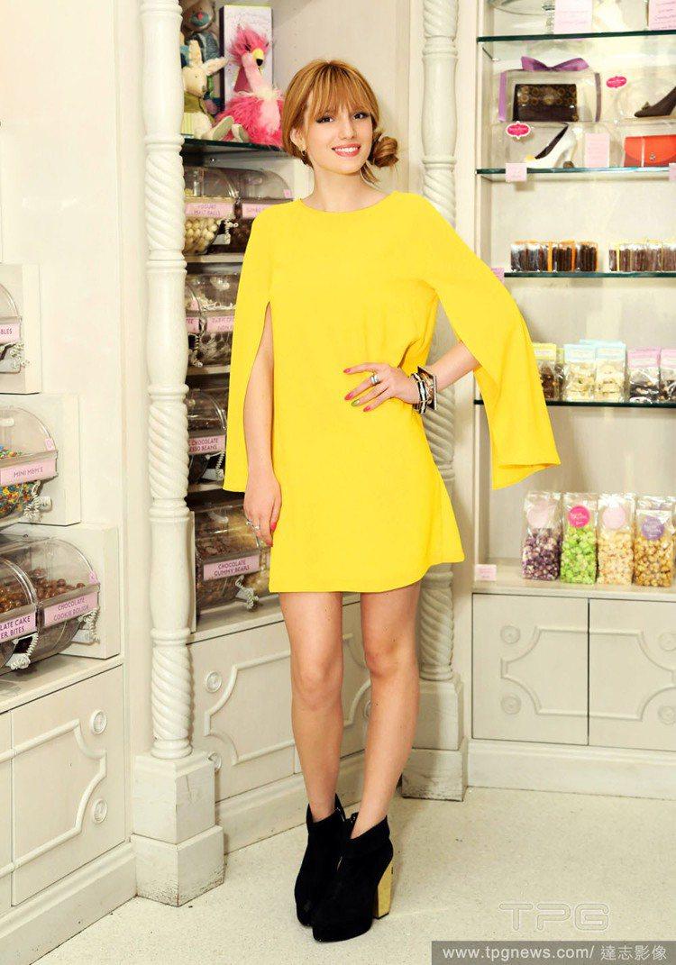 Bella Thorne穿著一身鮮黃色連身裙,腳踩黑色高跟短靴,並盤起秀髮打造開...