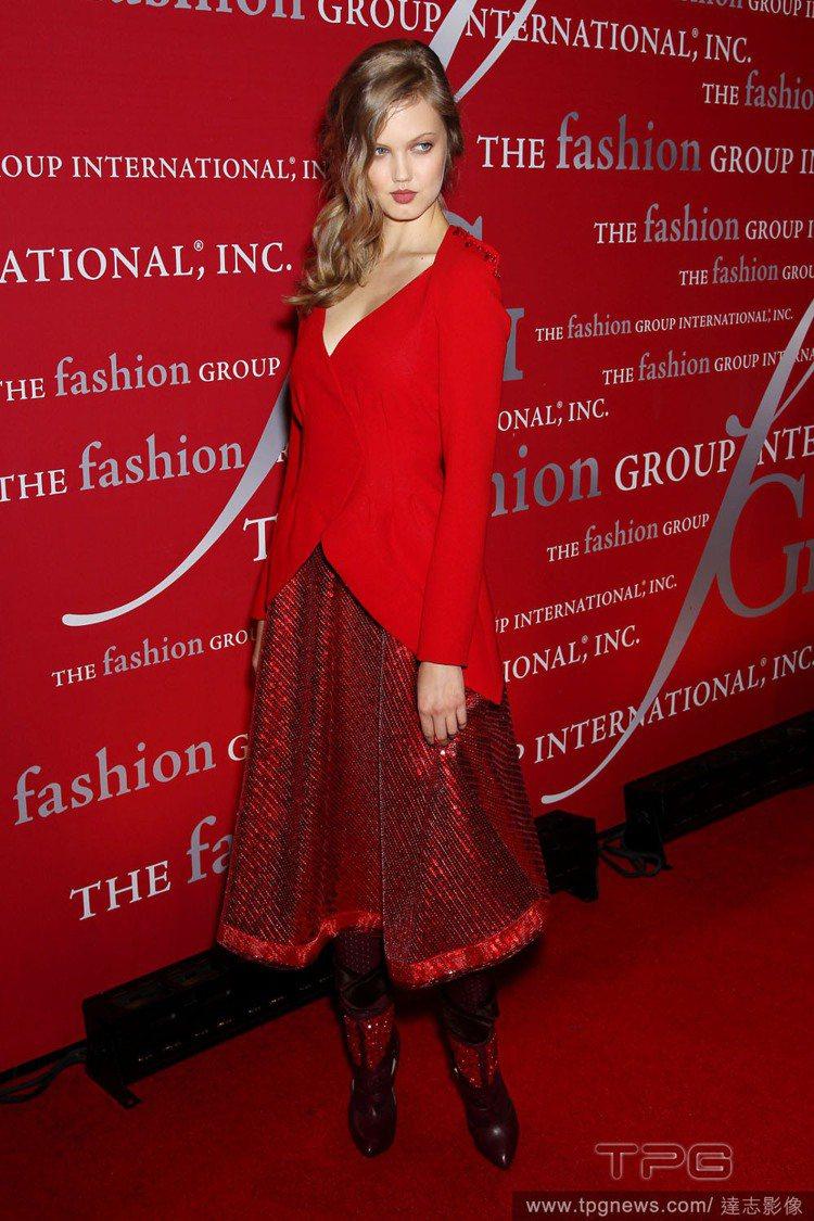 Lindsey Wixson喜歡以俐落簡單的外套搭配裙裝。火紅色外套與閃耀華麗紅...