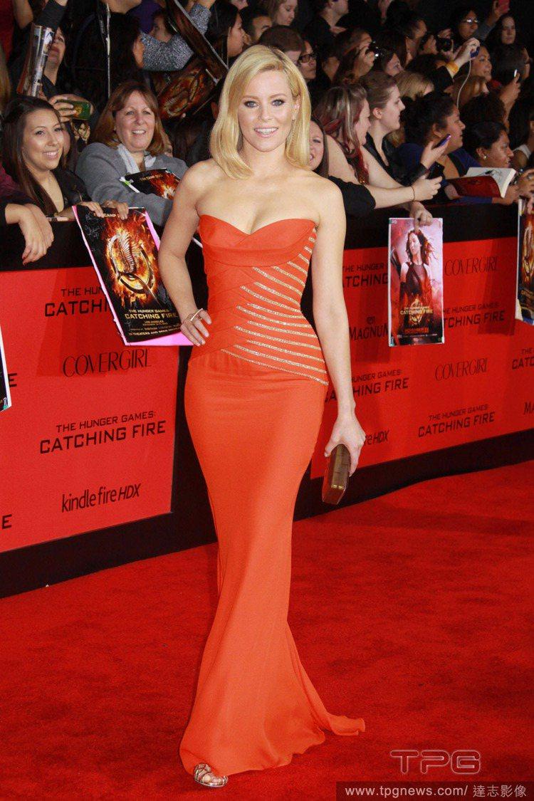 伊莉莎白一身的 Versace 亮橘色魚尾禮服,亮片與布料交疊成閃亮紋路,隨著身...