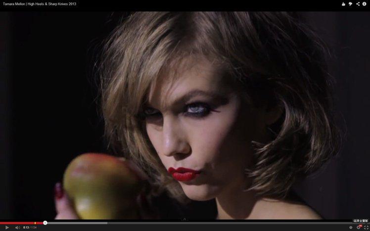 高挑纖細的 Karlie Kloss 穿著高跟鞋站在窗邊,嘴上一抹紅唇與尖銳詭異...