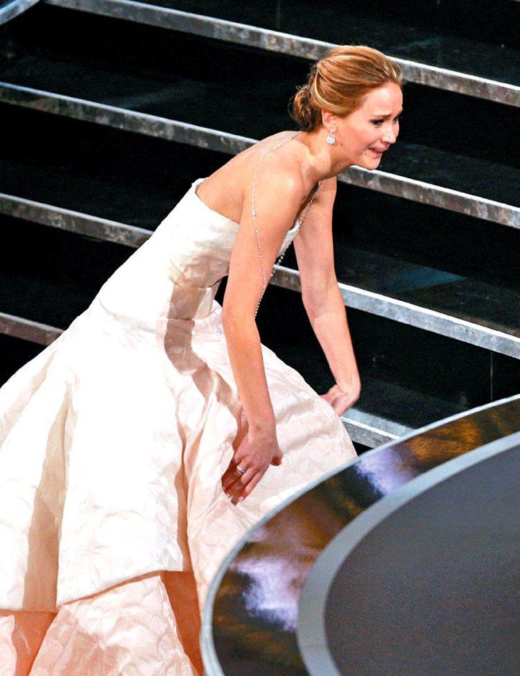珍妮佛勞倫斯年初在奧斯卡頒獎典禮上那一摔,摔出了人氣與片約,也讓她當時穿著的 D...