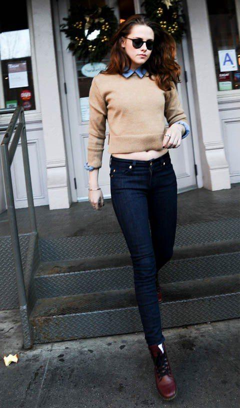克莉絲汀史都華將淺色丹寧襯衫穿在駝色針織衫裡,和諧的配色和質樸的布料再加上簡單的...