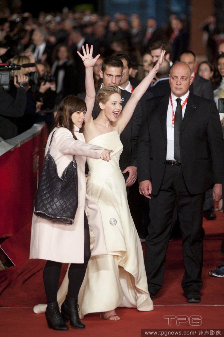 在羅馬《飢餓遊戲 2:星火燎原》首映會中,珍妮佛勞倫斯忙著跟影迷打招呼,大動作舉...