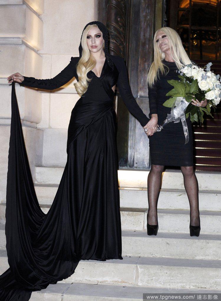 女神卡卡穿著一件Versace腰間鏤空的 V 領黑禮服小露性感,並拎起她的古典風...