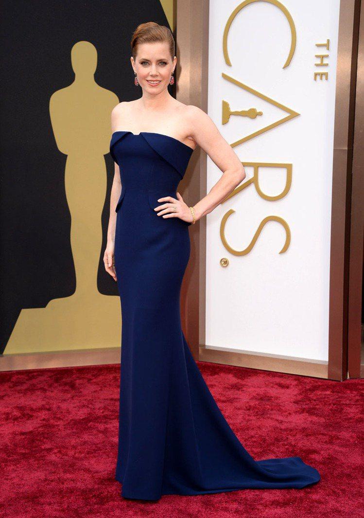 艾美亞當斯一改平日最愛的古典風格,選了 GUCCI 的深藍色平口禮服,以摩登俐落...