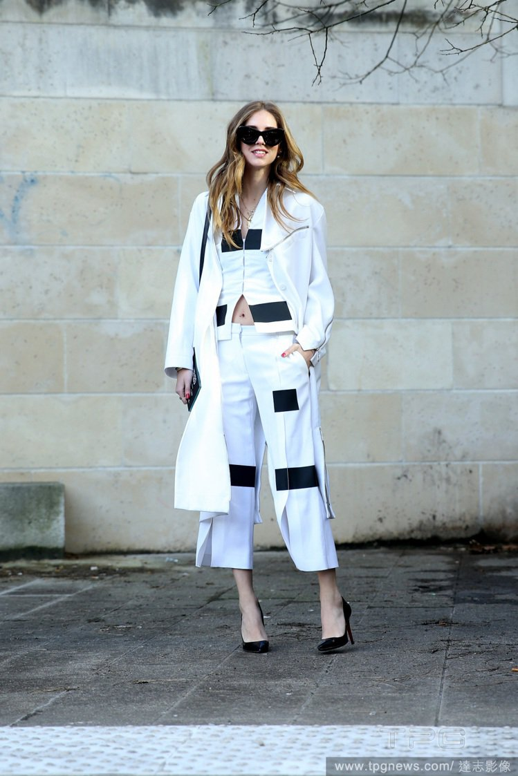 Chiara Ferragni 套上白色大衣,內搭有幾何色塊的白色褲裝與黑色高跟...
