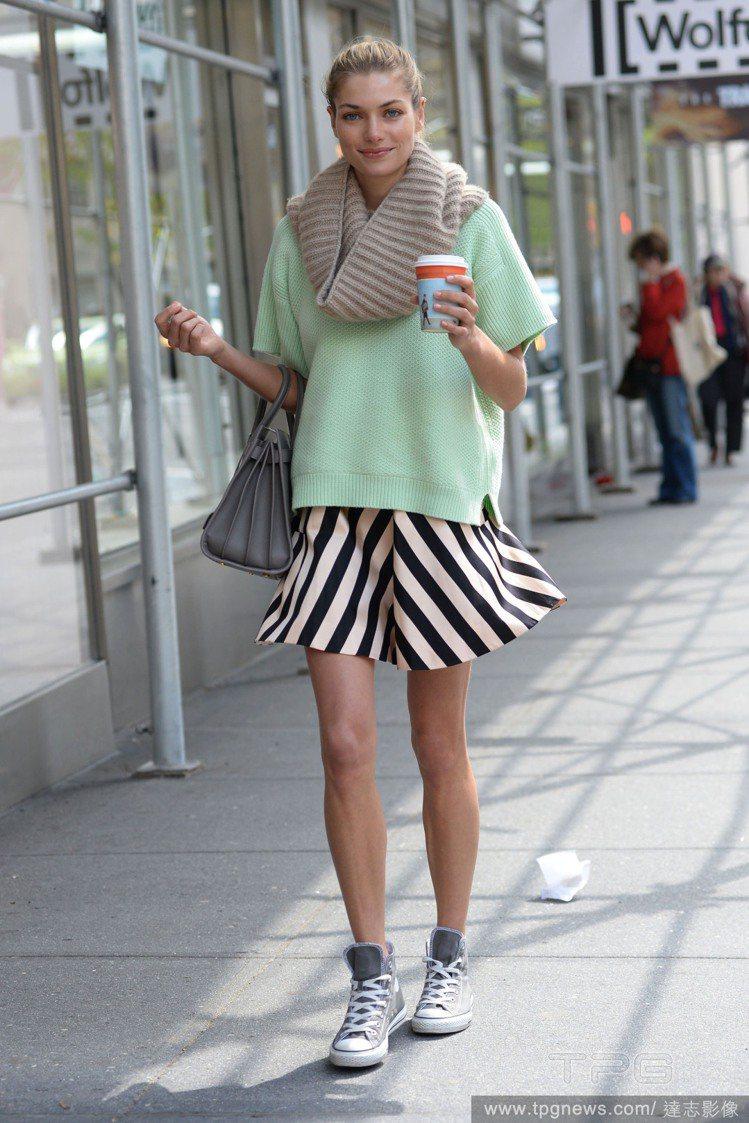 Jessica Hart 身穿薄荷綠上衣搭配黑白幾何條紋裙、灰色帆布鞋,散發俏麗...