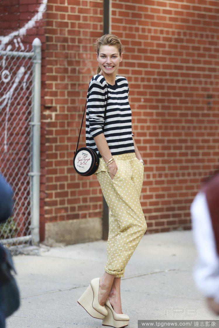 Jessica Hart 身穿黑白條紋衣搭配芥末黃點點褲,搭配楔型鞋與造型包款不...