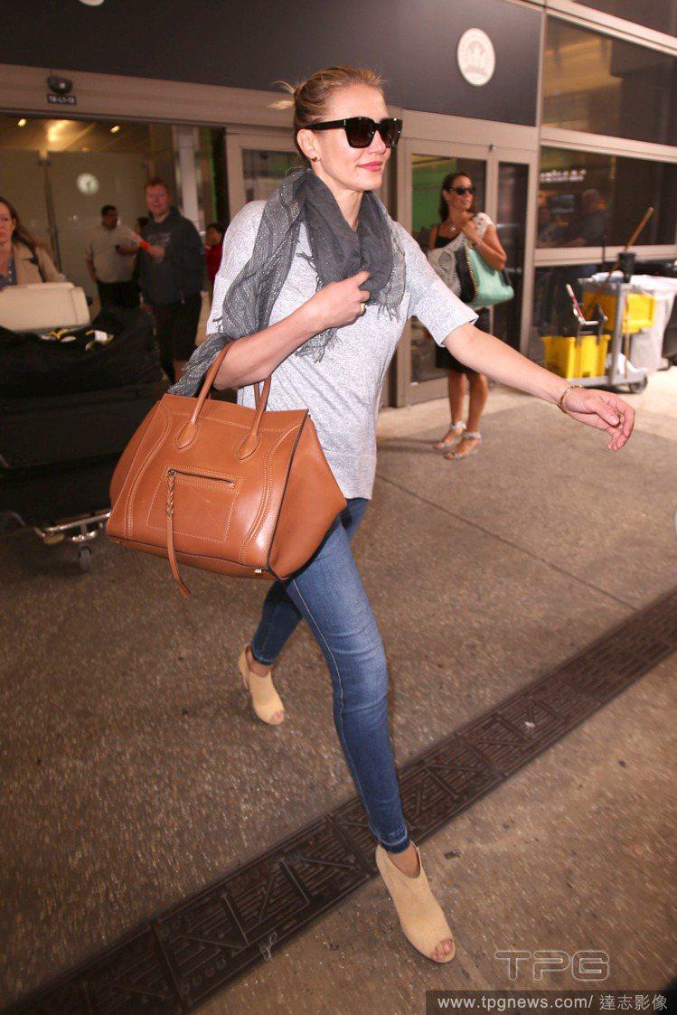 卡麥蓉狄亞茲手拎咖啡色 Celine luggage 包,搭配一身牛仔褲勁裝,顯...