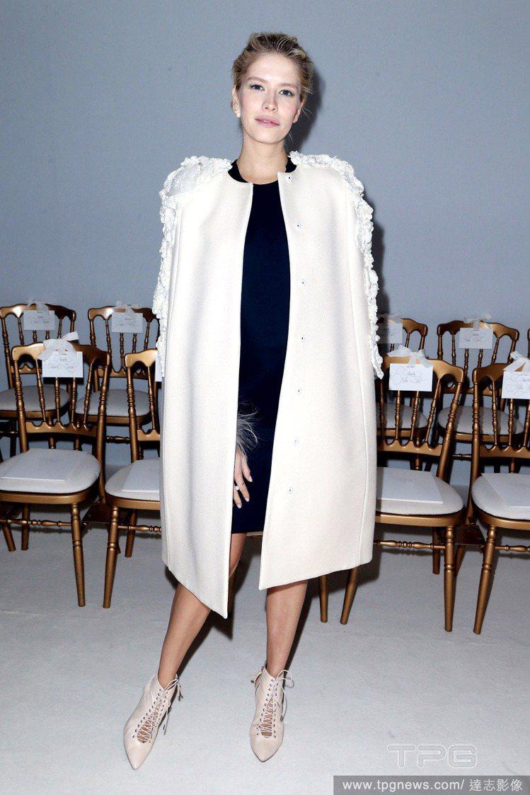 黑色連身裙搭配白色大衣,肩膀的雕花裝飾讓大衣更浪漫俐落,搭配裸色尖頭繫帶踝靴,為...