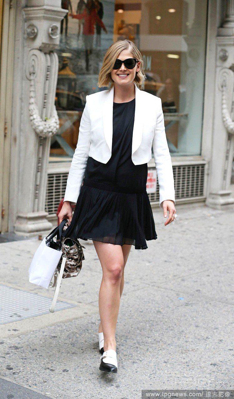 羅莎蒙派克以小黑洋裝搭配短版白色外套,黑白雙色尖頭鞋成為一抹亮點,展現簡單摩登的...