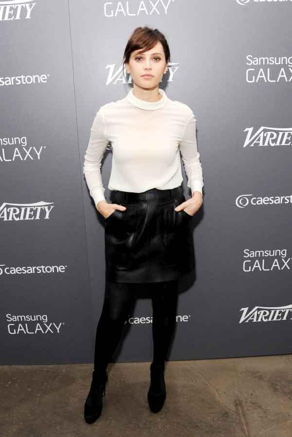 Felicity Jones以白色高領衫,簡單搭配黑裙、黑褲襪與黑鞋,打造瀰漫法...
