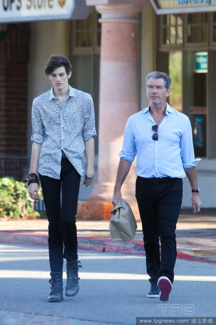 剛過18歲生日的迪倫布洛斯南,穿著花襯衫搭窄管褲與高筒鞋,陪老爸上街買東西。圖/...