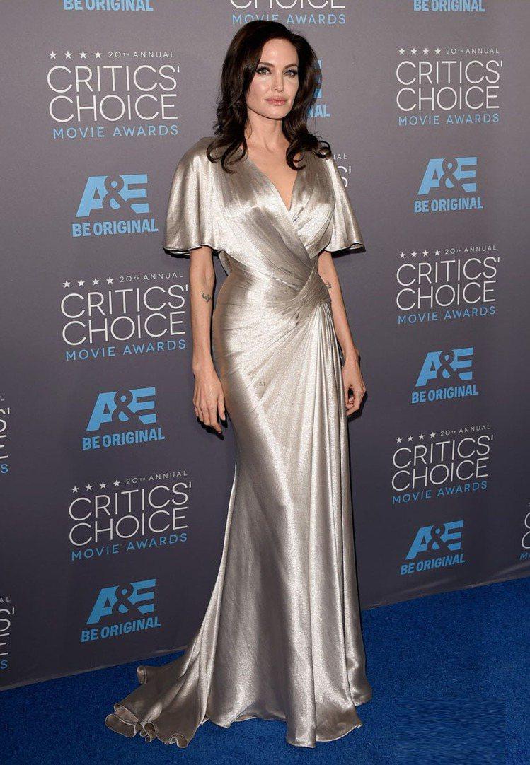 安潔莉娜裘莉則選了她最愛的 VERSACE 銀色禮服,展現古典好萊塢式的奢華。圖...